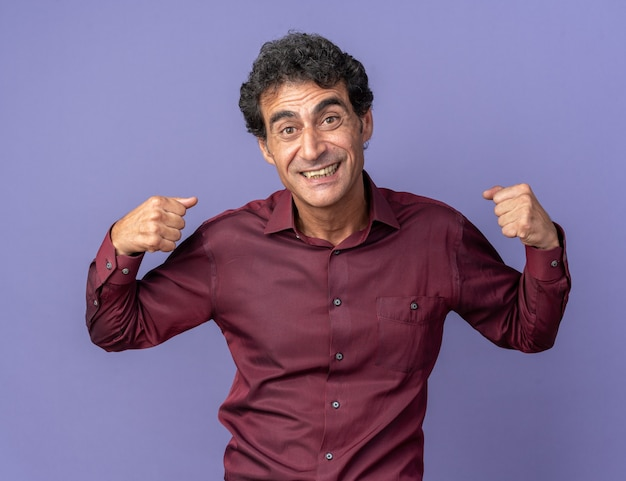 Senior man in purple shirt looking at camera happy and excited clenching fists standing over blue background
