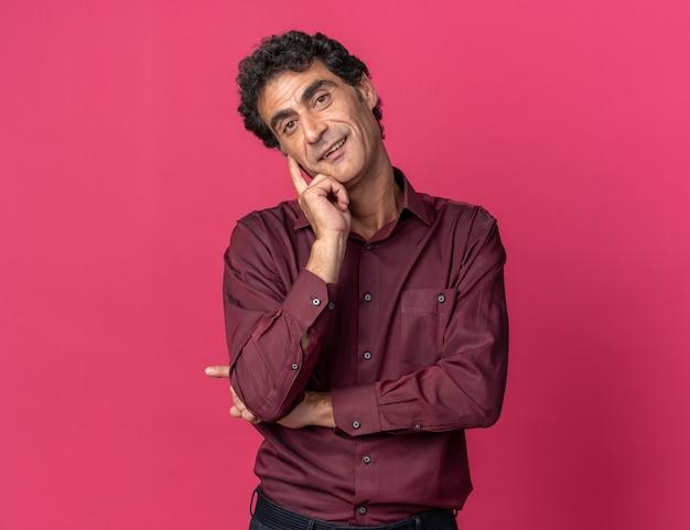 Uomo anziano in camicia viola che guarda la telecamera felice e contento che sorride allegramente in piedi su sfondo rosa