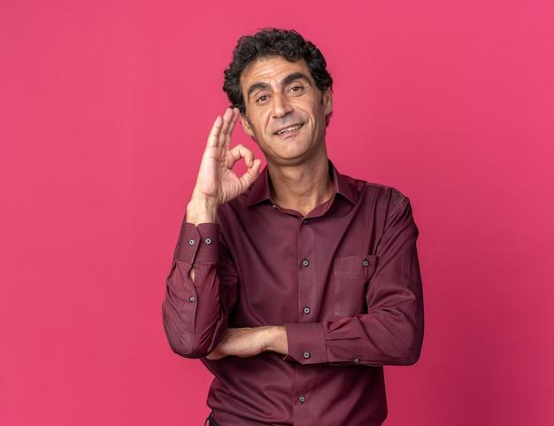 Uomo anziano in camicia viola che guarda la telecamera felice e positivo facendo segno ok sorridendo allegramente in piedi su sfondo rosa