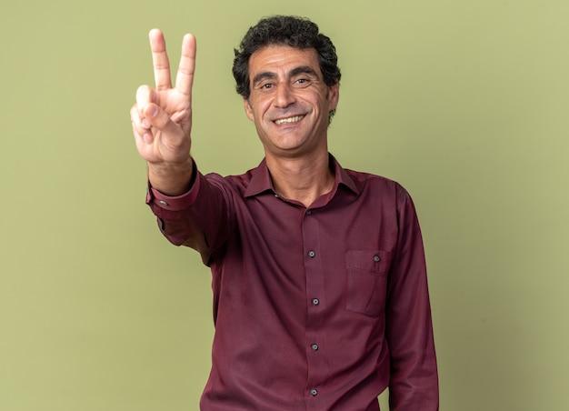 Uomo anziano in camicia viola che guarda l'obbiettivo sorridendo allegramente mostrando il v-sign