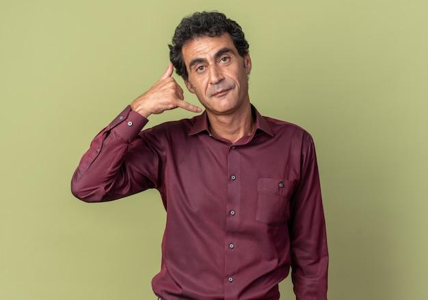 Uomo anziano in camicia viola che guarda la telecamera sorridendo fiducioso che mi chiama gesto