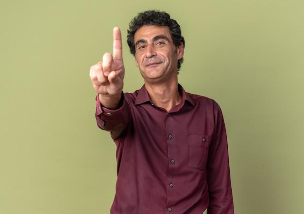 Uomo anziano in camicia viola che guarda la telecamera sorridendo fiducioso che mostra il dito indice