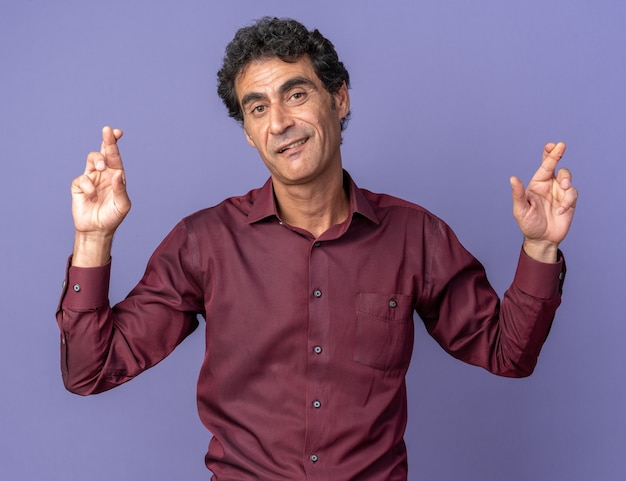 Senior man in purple shirt looking at camera smiling making wish crossing fingers standing over blue background