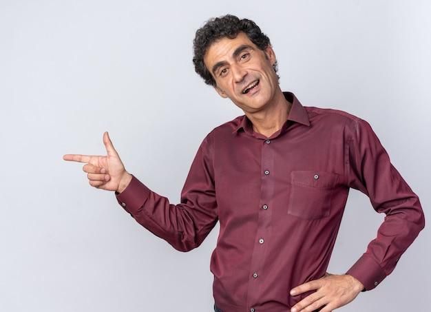 Uomo anziano in camicia viola che guarda la telecamera sorridente che punta con il dito indice a lato in piedi su sfondo bianco