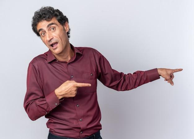 Uomo anziano in camicia viola che guarda la telecamera sorpresa indicando con l'indice il lato in piedi su sfondo bianco