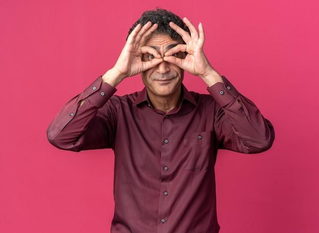 Uomo anziano in camicia viola che guarda la telecamera attraverso le dita facendo un gesto binoculare sorridente in piedi su sfondo rosa
