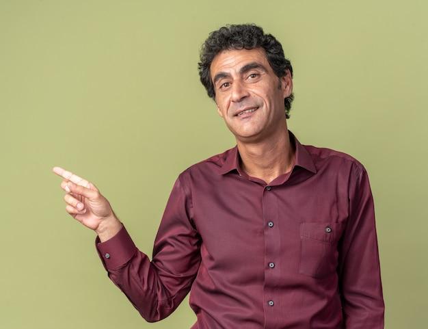 Uomo anziano in camicia viola che guarda la telecamera con un sorriso fiducioso sul viso che punta con il dito indice sul lato in piedi sul verde