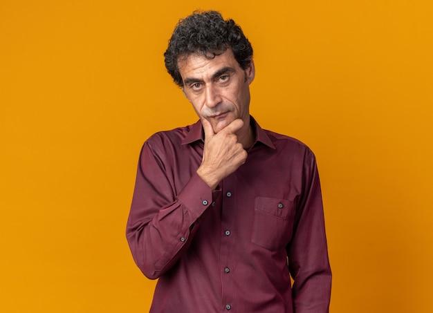 Uomo anziano in camicia viola che guarda la telecamera con la mano sul mento pensando in piedi sopra l'arancia