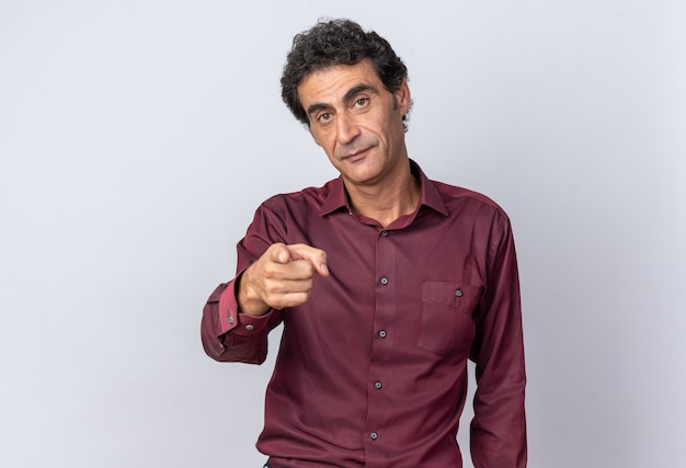 Uomo anziano in camicia viola che guarda la telecamera con una faccia seria che punta con il dito indice verso la telecamera in piedi su sfondo bianco