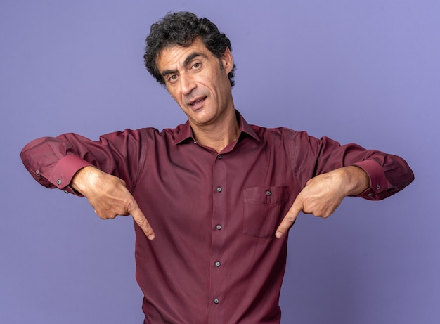 Senior man in purple shirt looking at camera with serious face pointing with index fingers down standing over blue background