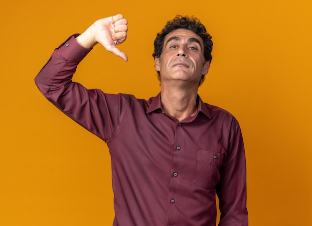 Senior man in purple shirt looking at camera with serious face showing thumbs down standing over orange