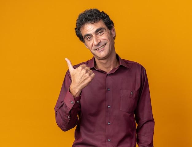Uomo anziano in camicia viola che guarda la telecamera con un sorriso sulla faccia felice che punta con il pollice di lato