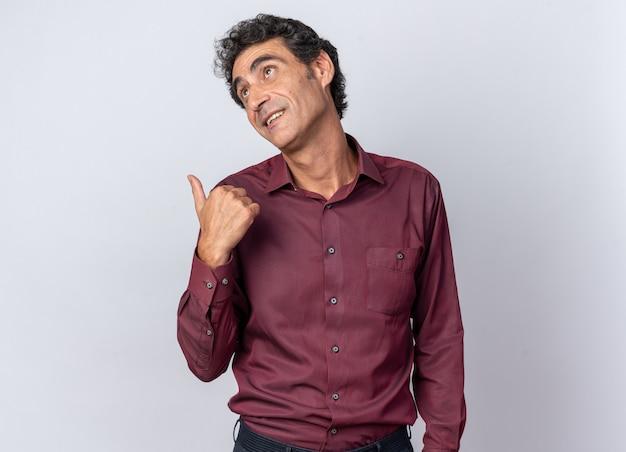 Uomo anziano in camicia viola che sembra sorridente fiducioso che punta indietro con il pollice in piedi sopra il bianco