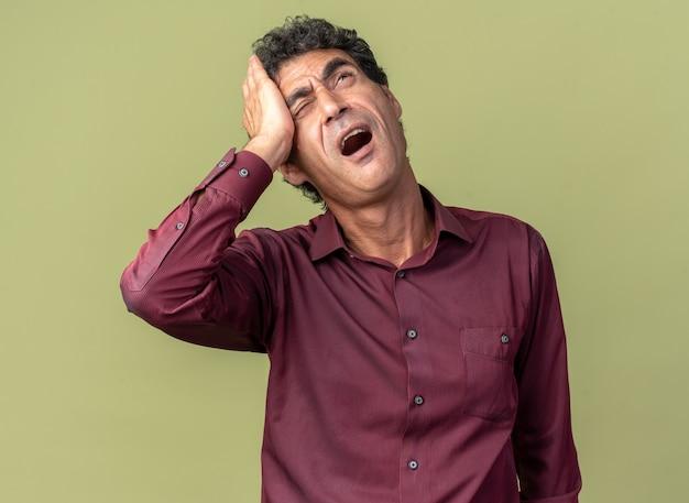Uomo anziano in camicia viola che sembra confuso e dispiaciuto con la mano sulla testa per errore in piedi su sfondo verde