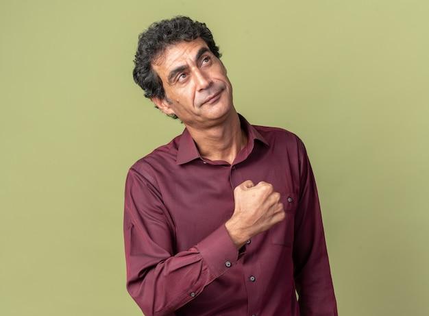 Uomo anziano in camicia viola che guarda felice e compiaciuto il pugno serrato in piedi su sfondo verde
