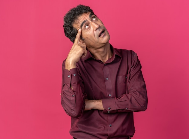 Uomo anziano in camicia viola che guarda perplesso grattandosi la testa in piedi su sfondo rosa