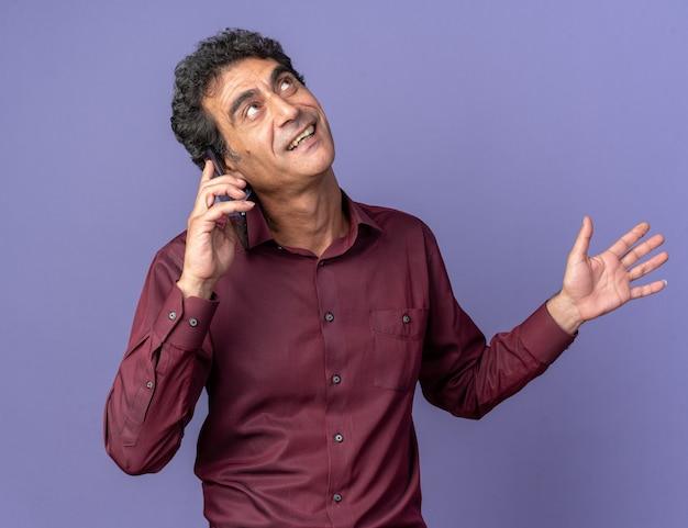 Uomo anziano in camicia viola che guarda in alto sorridendo allegramente mentre parla al telefono cellulare in piedi su sfondo blu