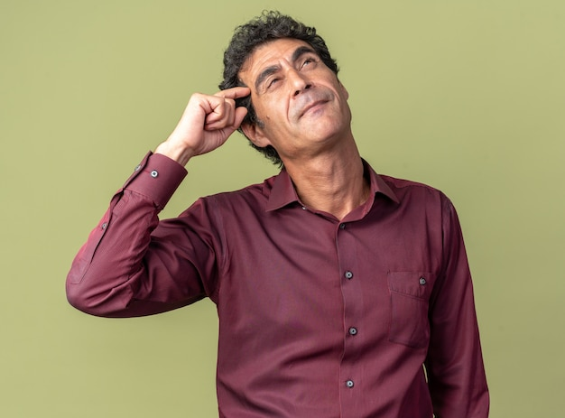 Senior man in purple shirt looking up with pensive expression thinking scratching his head standing over green background