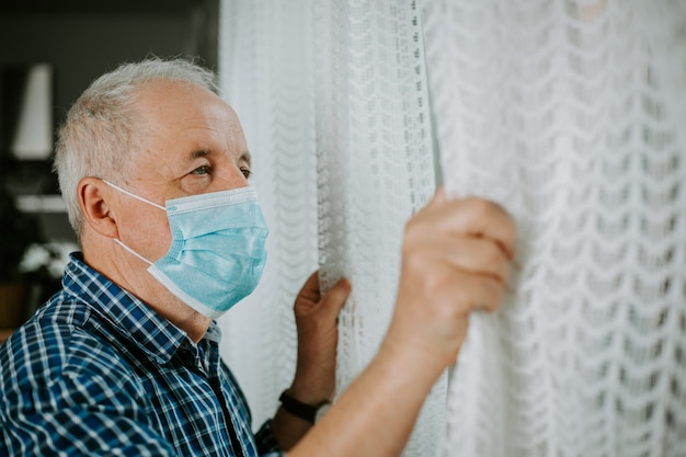 Senior man quarantined at the home during coronavirus pandemic, stay safe