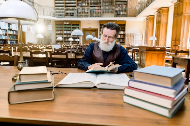 Senior man reader sits in luxury ancient library interior and reads book. bearded man with happy face enjoys reading.