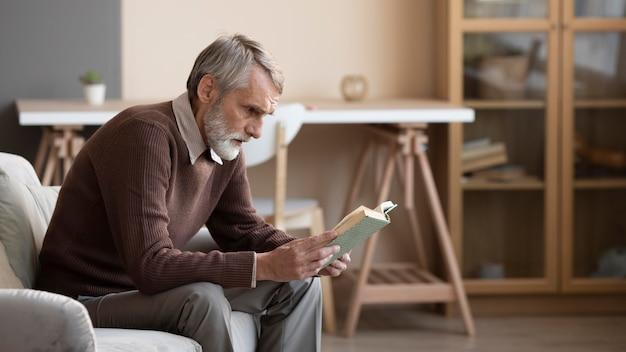 家で本を読んでいる年配の男性