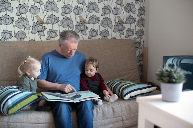 작은 여자에 게 책을 읽고 수석 남자입니다. 소파에서 손녀와 시간을 보내는 할아버지.