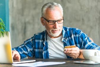 Senior man reading credit card number while working on laptop