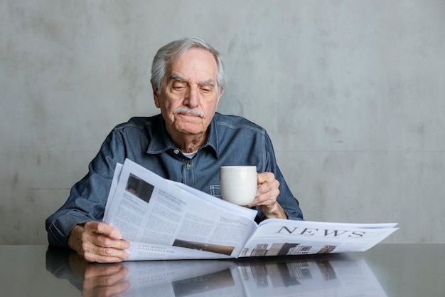 Senior man reading the news and drinking coffee