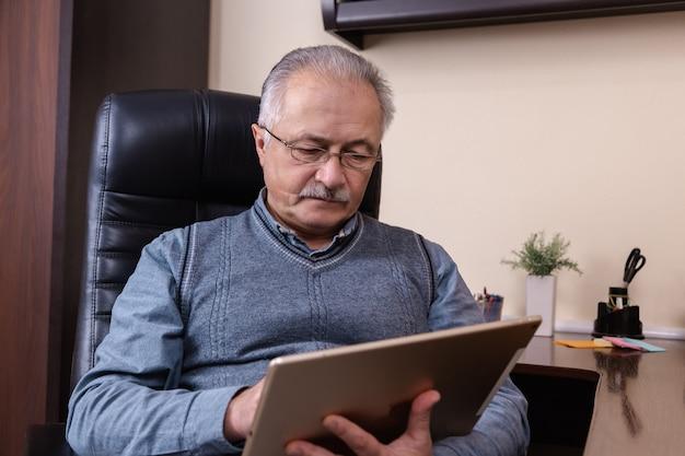 디지털 태블릿에 뉴스를 읽는 수석 남자. 집에서 책상에 앉아 태블릿을 사용 하여 수석 남자. 현대 기술, 통신 개념