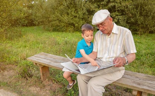 新聞を読んでいる年配の男性と公園のベンチに座っている彼の指で記事を指しているかわいい子供。 2つの異なる世代の概念。
