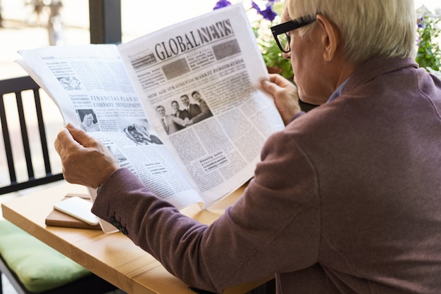 Газета чтения старшего человека на завтраке