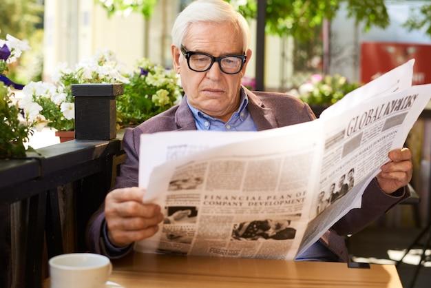 Пожилой мужчина читает газету в кафе