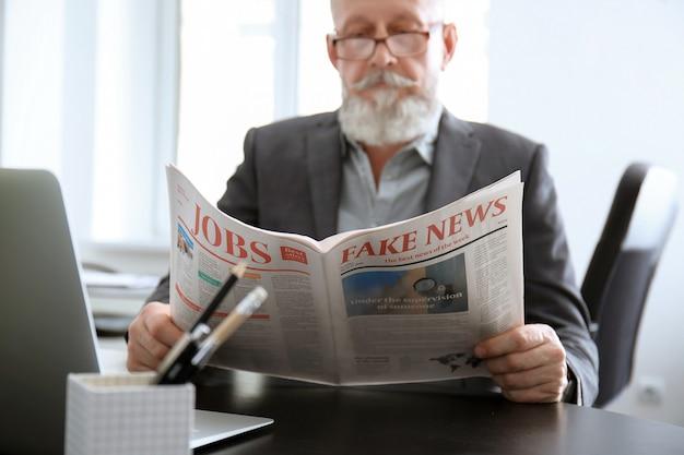 Senior man reading newspaper in office