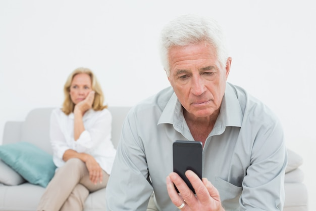 Senior man reading text message with woman at home