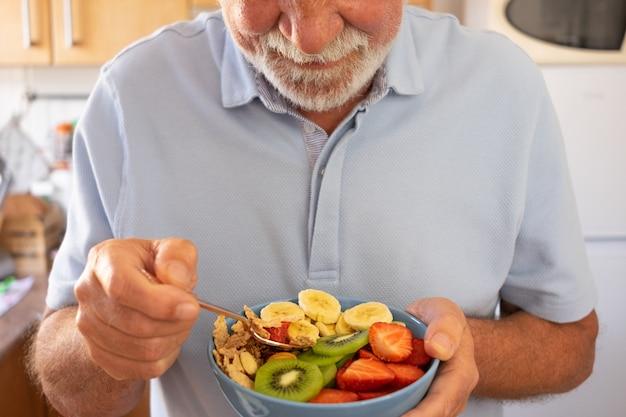 新鮮なドライフルーツのサラダを食べる準備ができている年配の男性。朝食または昼食時間、健康的な食事