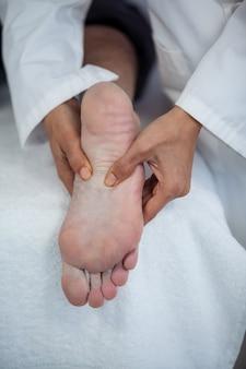 理学療法士から足裏マッサージを受けるシニア男性