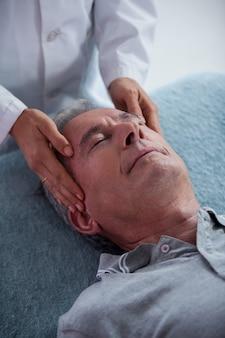 Senior man receiving head massage from physiotherapist