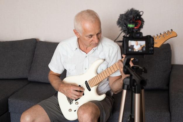 Старший мужчина записывает музыкальное видео в блоге, играет на гитаре, сидя на диване у себя дома