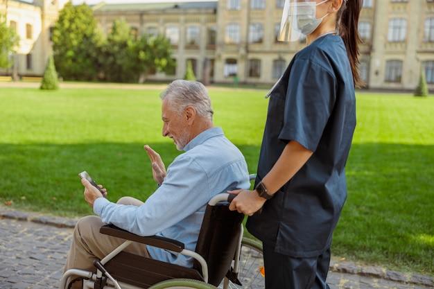 一緒に歩きながらスマートフォンを使用してビデオ通話を行う車椅子で患者を回復する年配の男性