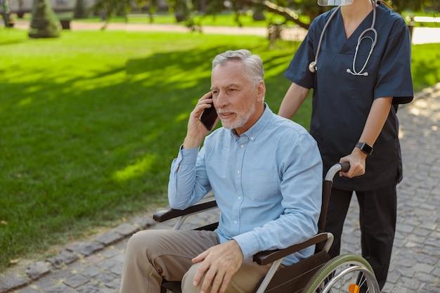 で看護師と一緒に歩いている間、電話で話している車椅子で患者を回復している年配の男性