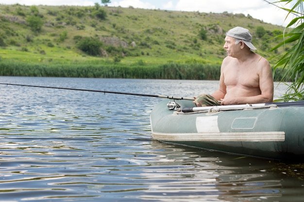 Senior man relaxing fishing from a dinghy