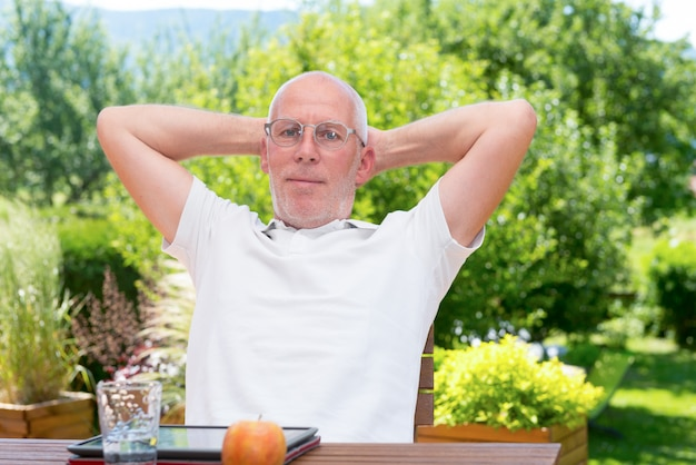 Старший мужчина отдыхает в очках, в своем саду