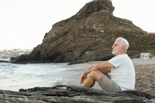 Senior man resting at the beach and admiring the ocean