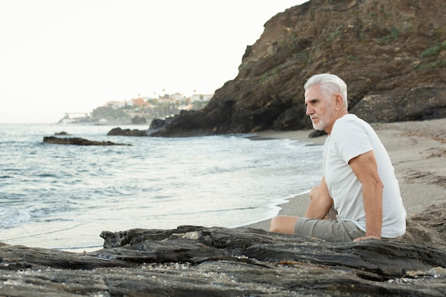 Senior man resting at the beach and admiring the ocean Free Photo
