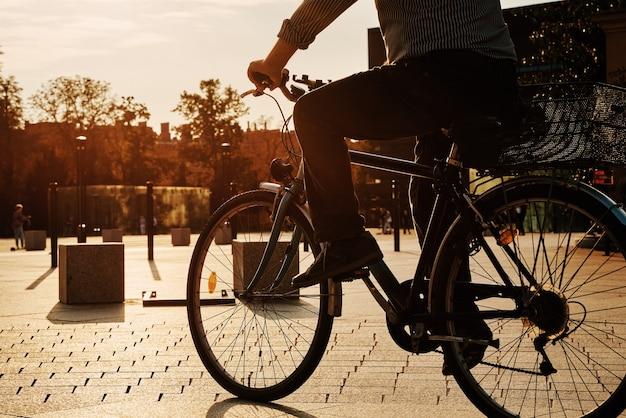 Старший мужчина ездит на велосипеде по городской улице