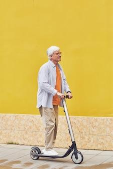 Старший мужчина на скутере на желтом