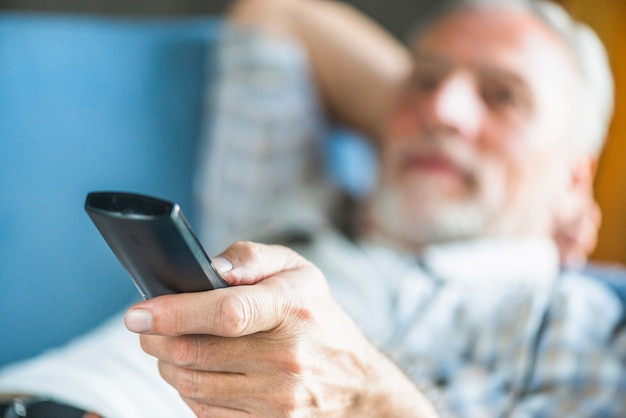 Senior man's hand holding remote control