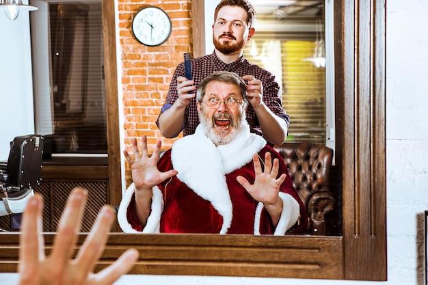Senior man in santa claus costume shaving his personal master at barber shop before christmas