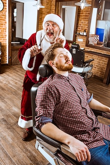 The senior man in santa claus costume working as personal master with scissors at barber shop before christmas