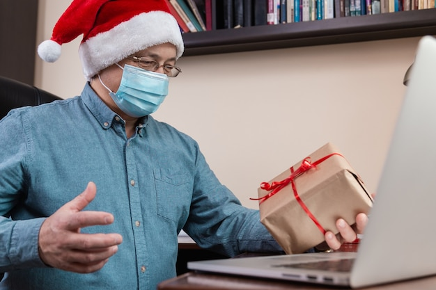Senior man in santa claus hat and face mask gives a gift and talks using laptop for video call friends and childrens. christmas during coronavirus.